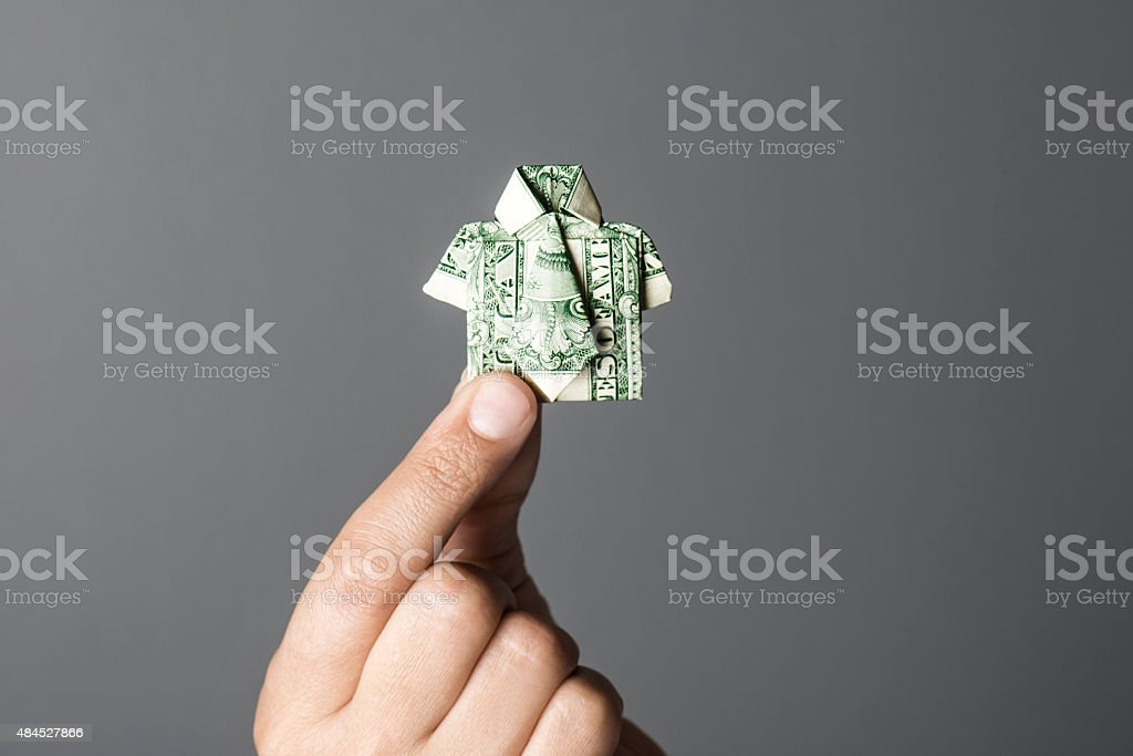 Origami One Dollar Shirt in Human Hand stock photo