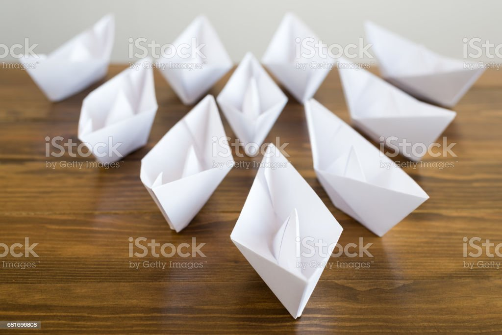 Origami white paper boats on a wooden table, soft focus.