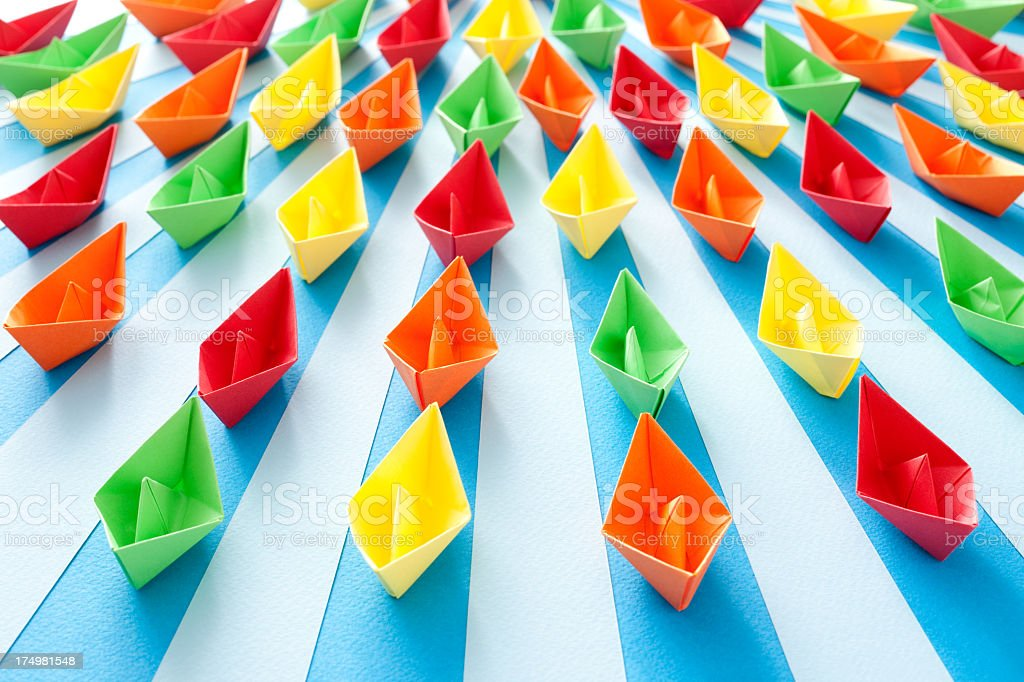 Representation of ships sailing at sea made with multicolored origami...