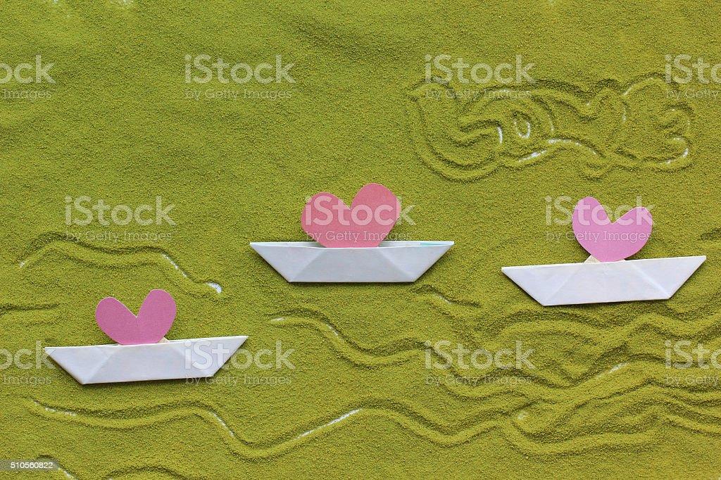 Origami sailboat and heart on green tea matcha stock photo