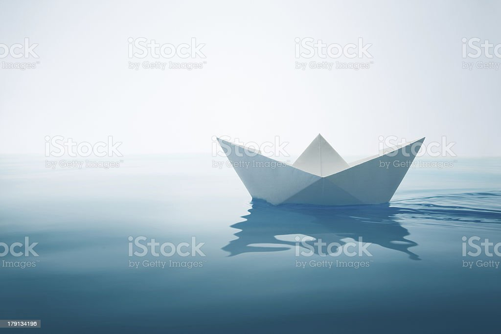 Origami sailboat floating in a glassy pool of water stock photo