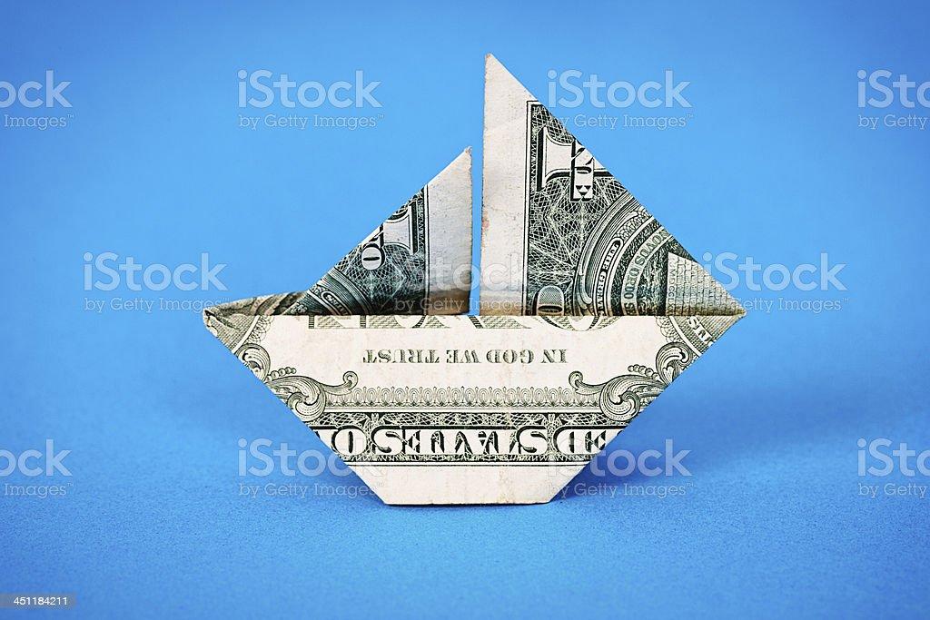 Origami sailboat folded from US dollar bill floats into blue stock photo