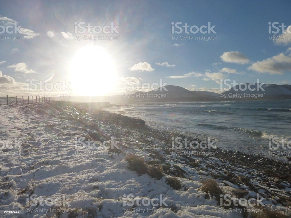 Orkney winter sun across the snow and sea stock photo