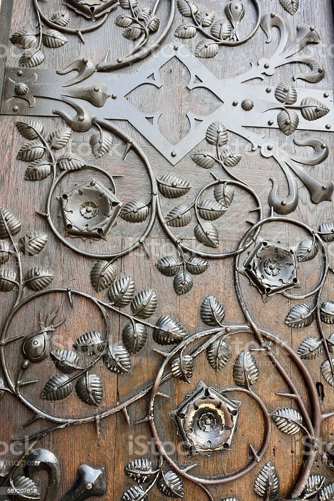 Ornamental ironwork on brown wooden door stock photo