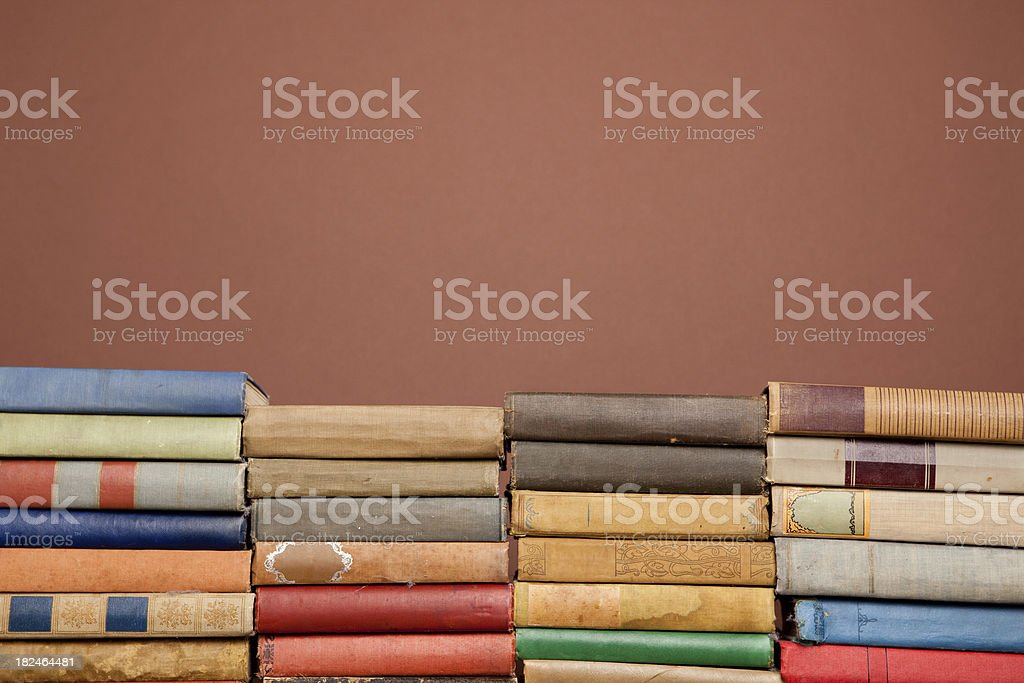 Ornate, Antique Books Lined in Front of Brown Background royalty-free stock photo