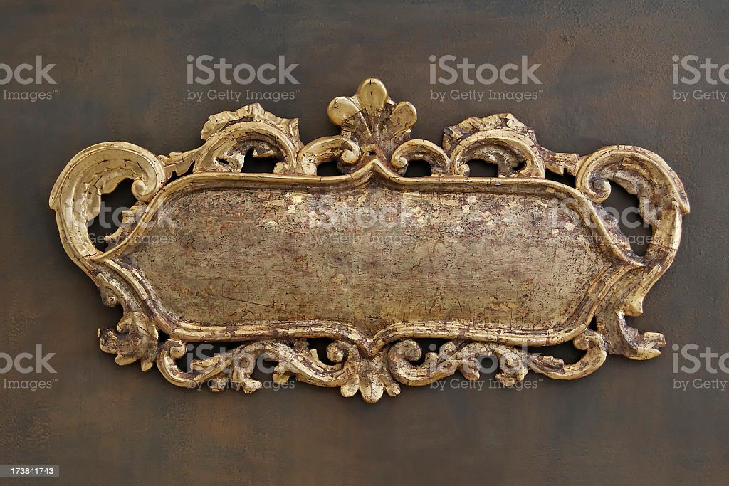 Ornate brass colored metal emblem on a brown wall stock photo