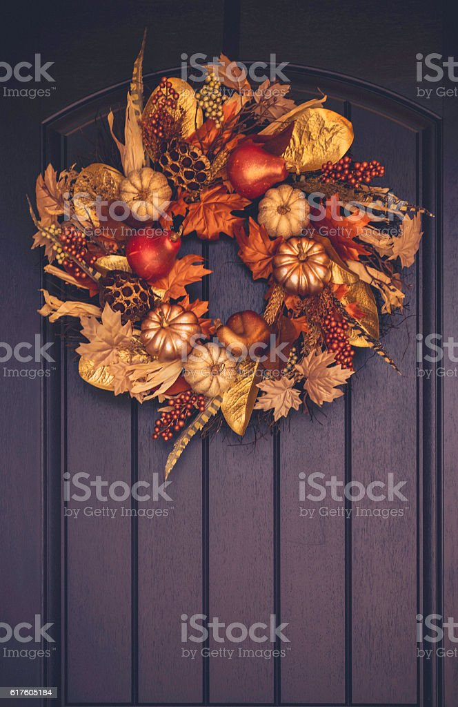 Ornate fall wreath with gold pumpkins hanging on front door stock photo
