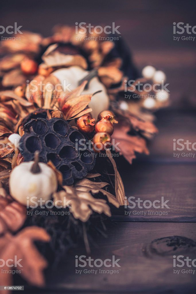 Ornate fall wreath with gold pumpkins laying on wood stock photo