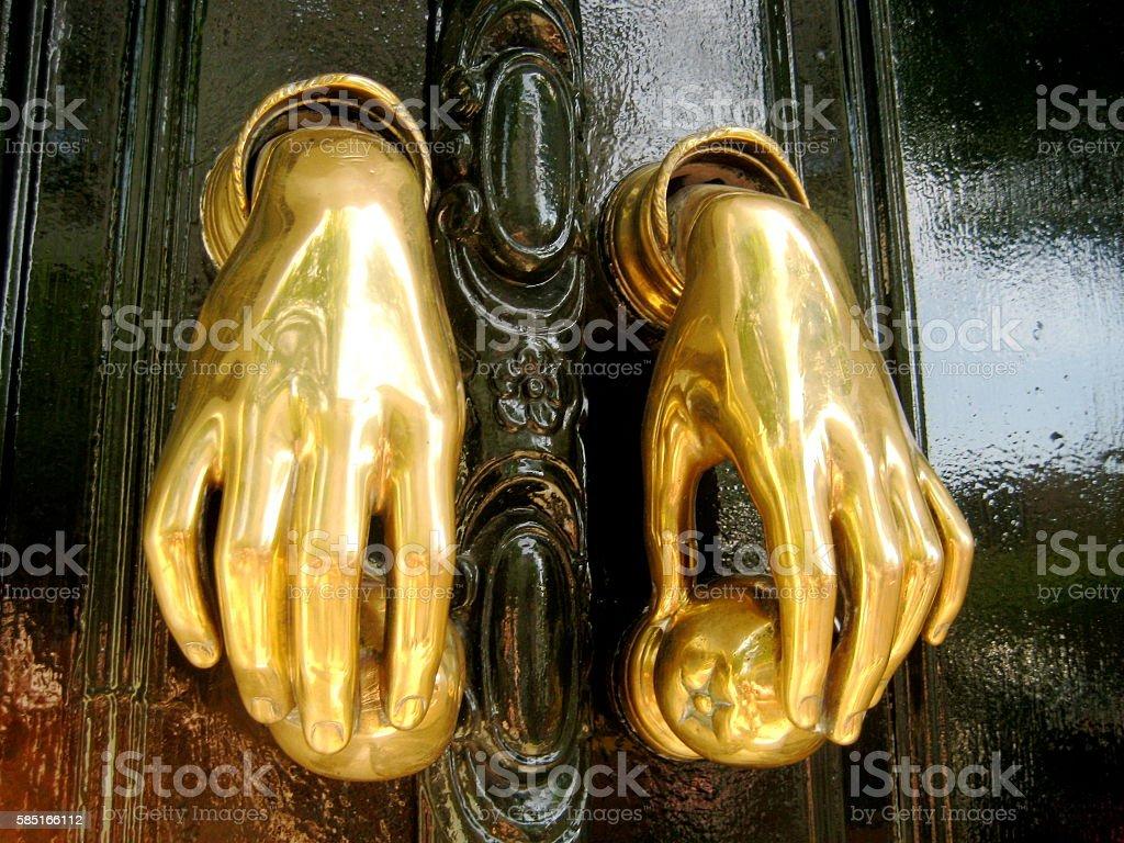Ornate gold hand door knockers stock photo