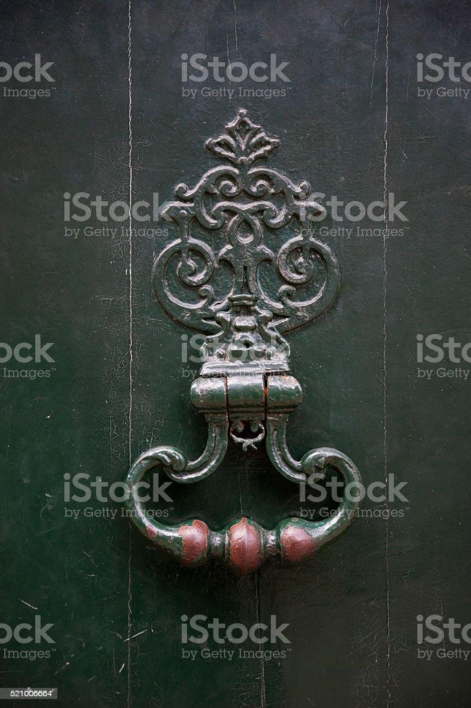 Ornate metal knocker on green door in France stock photo