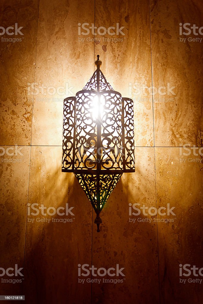 Ornate metal lamp on a marble wall royalty-free stock photo