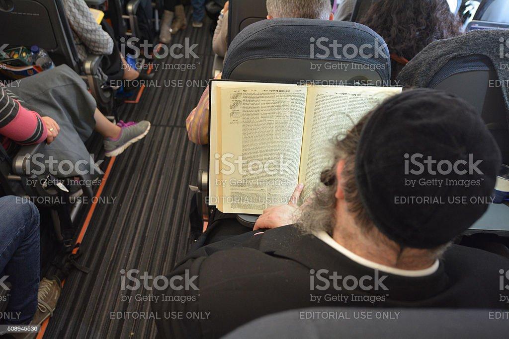 Orthodox Jewish Man Prays on Plane stock photo