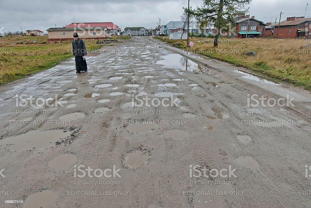 Orthodox monk goes along muddy street on Solovetsky Island, Russia. stock photo