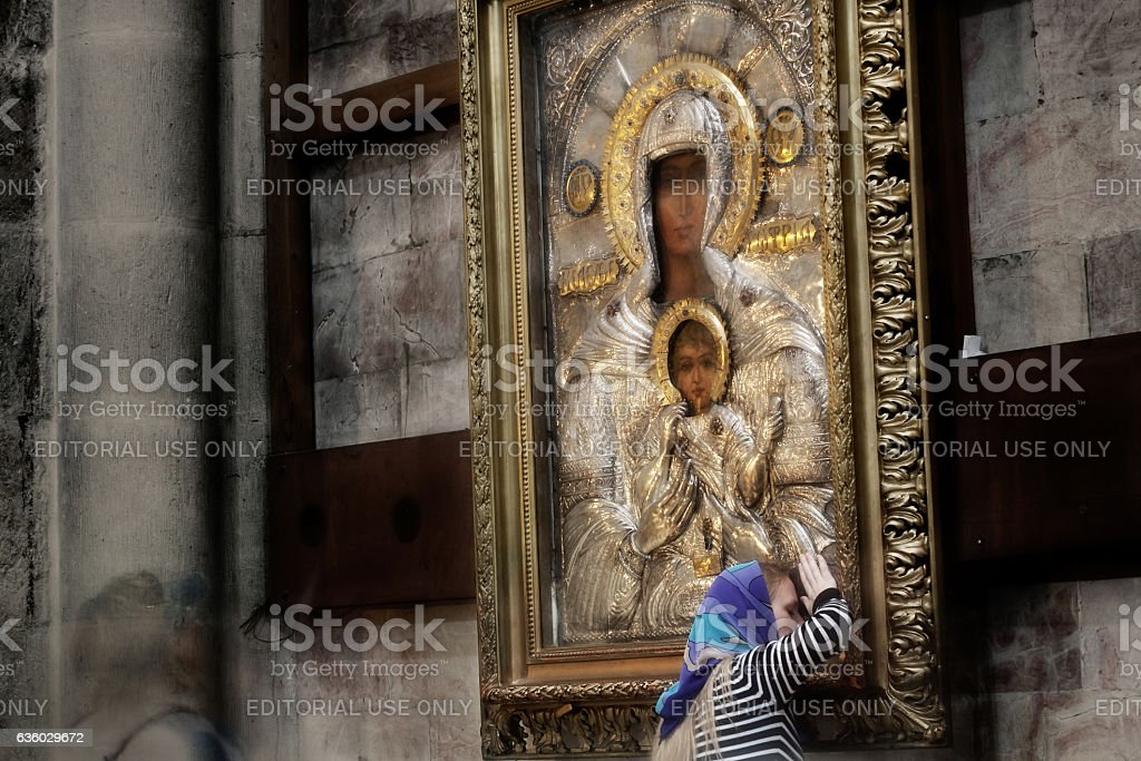 Orthodox pilgrim prays by the icon in Holy Sepulchre Church stock photo