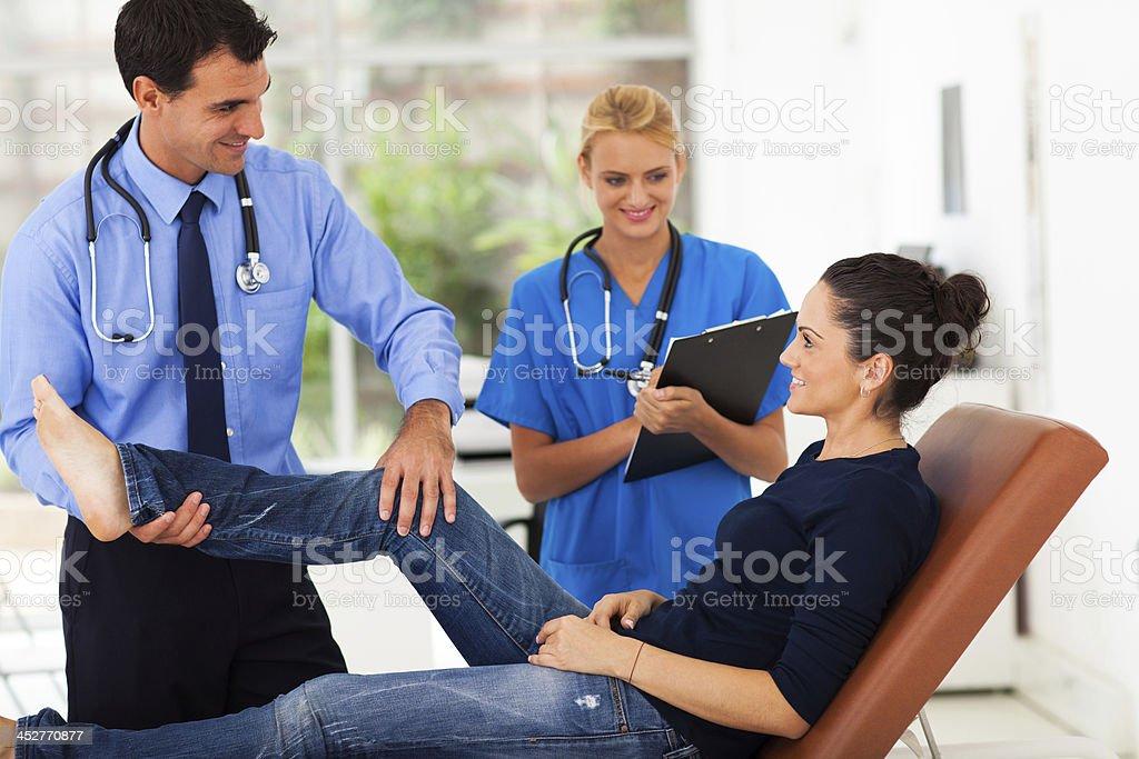 orthopaedist examining female patient's leg stock photo