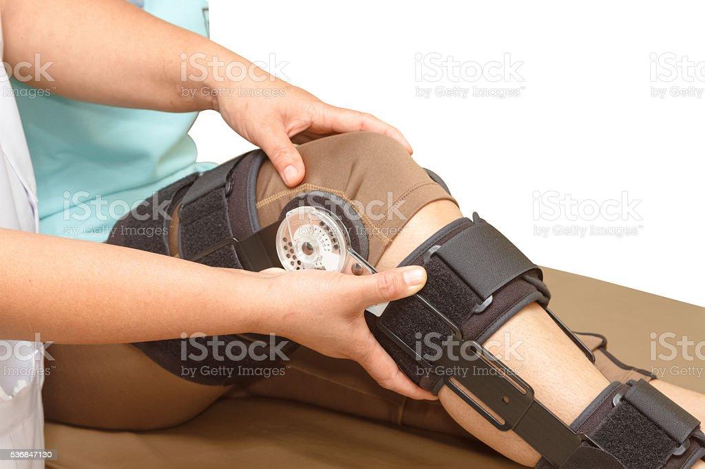 Orthopedist secures leg brace on knee, knee brace support f stock photo