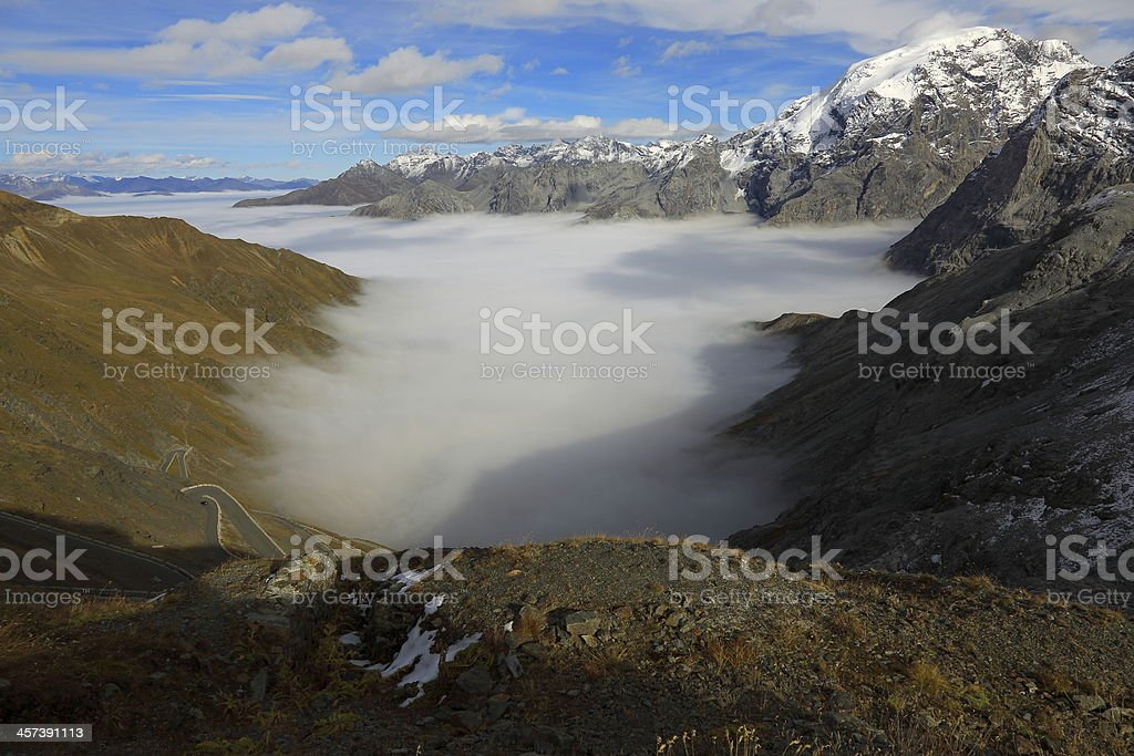 Ortler and above Stelvio Pass clouds mist - Italy stock photo