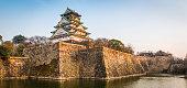 Osaka Castle walls and moat illuminated at sunset panorama Japan