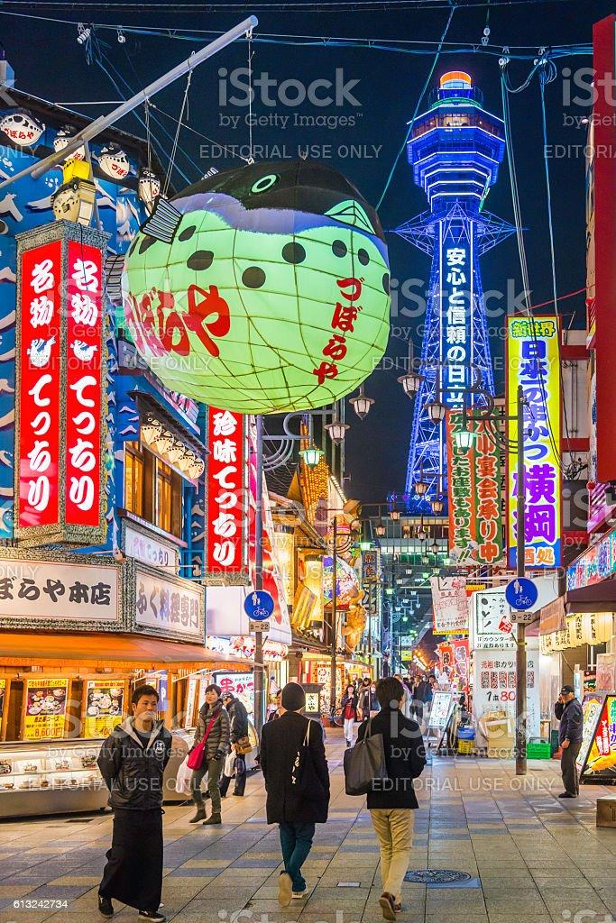Osaka neon night Tsutenkaku Tower overlooking people in Shinsekai Japan stock photo