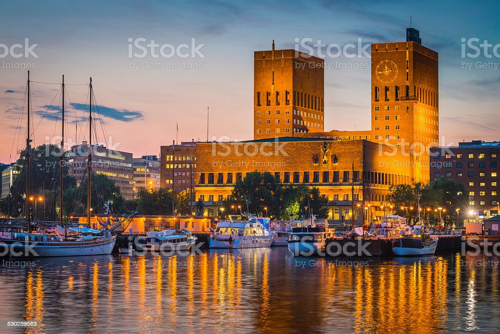 Oslo City Hall landmark towers overlooking illuminated harbour sunset Norway stock photo
