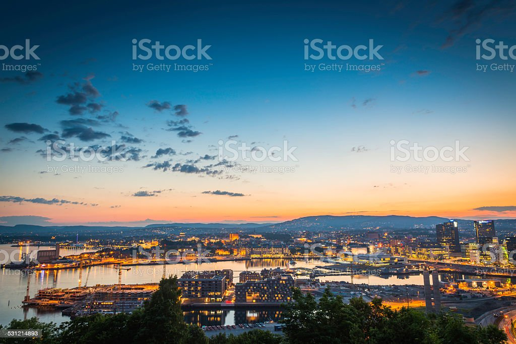 Oslo city lights illuminated under blue chrome dusk sky Norway stock photo