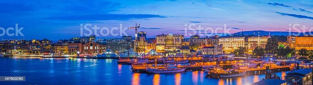 Oslo harbour sunset illuminated landmarks Aker Brygge waterfront panorama Norway stock photo