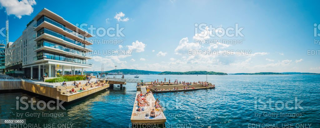 Oslo people enjoying summer sunbathing on Aker Brygge waterfront Norway stock photo