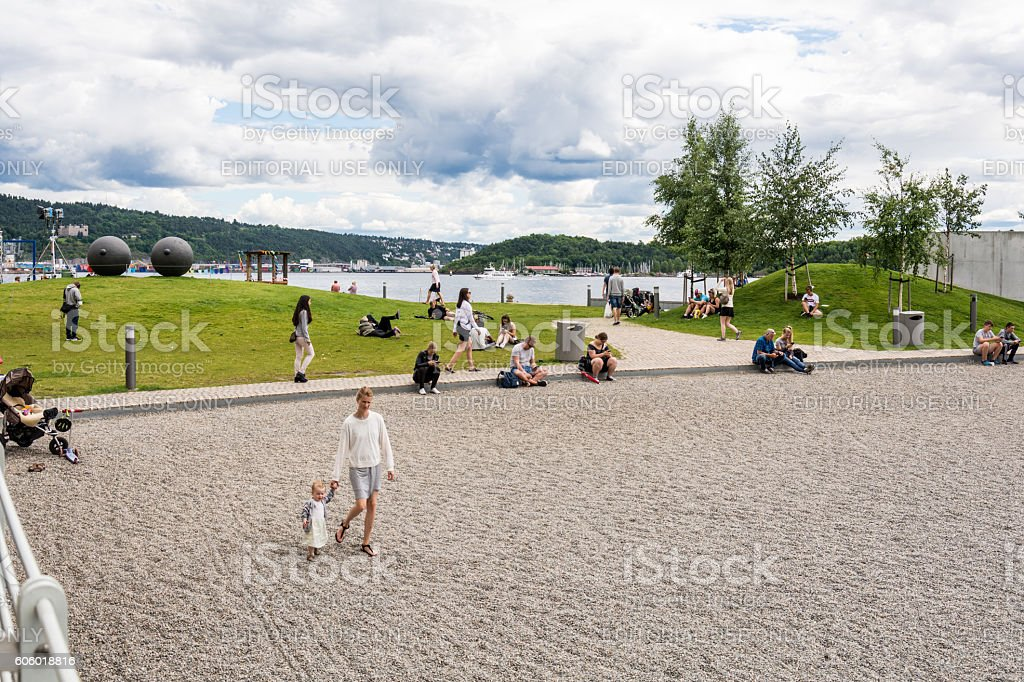 Oslo people on harbour beach Aker Brygge stock photo