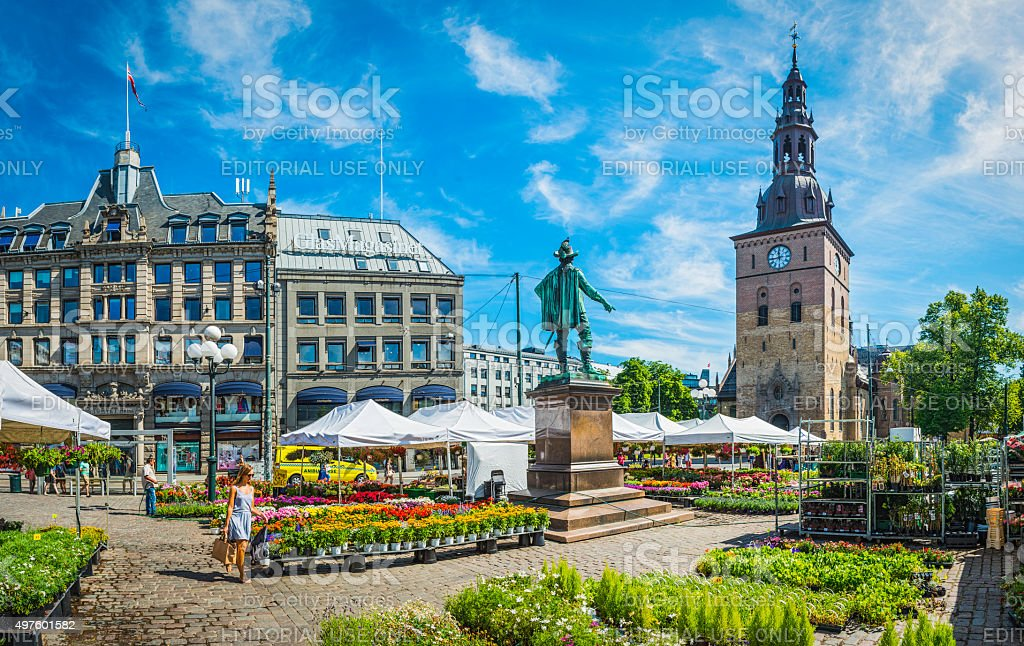 Oslo woman walking through flower market in square Stortovet Norway stock photo
