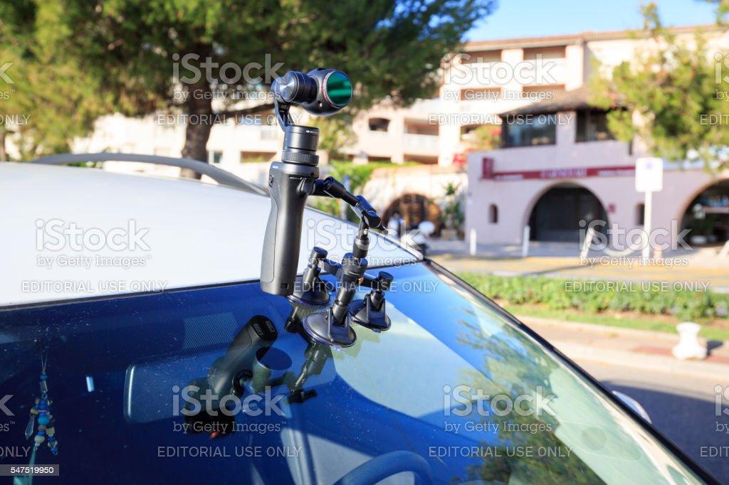 DJI Osmo handheld gimbal camera mounted on a car's windshield stock photo