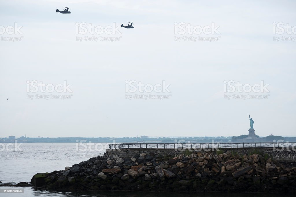 Osprey aircraft flying past Statue of Liberty in New York stock photo