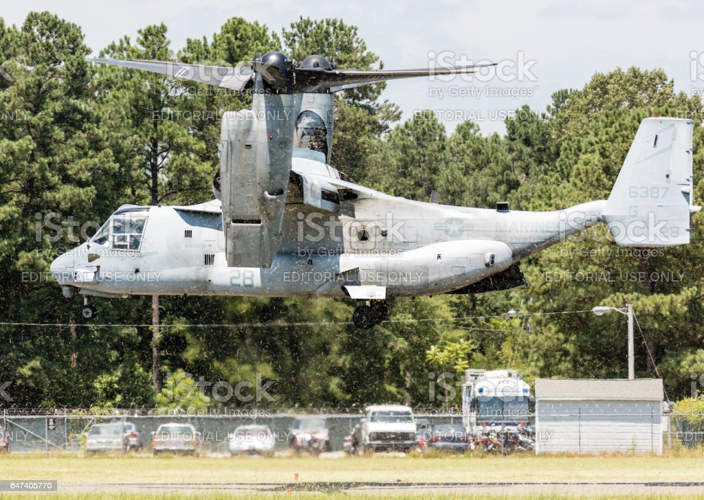 V-22 Osprey takes off in a cloud of grass clippings stock photo