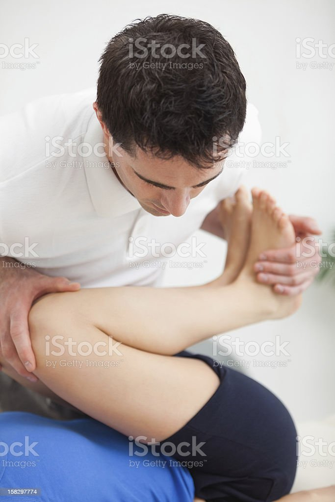 Osteopath bending the legs of a patient royalty-free stock photo