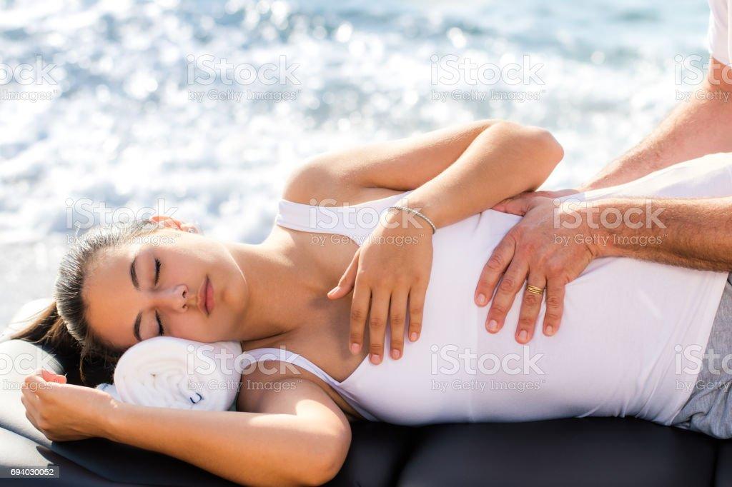 Osteopath doing manipulative treatment on female torso outdoors. stock photo