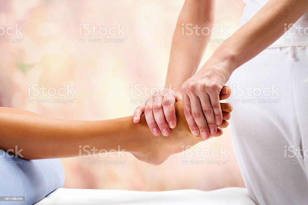 Osteopath doing reflexoloy massage on female foot. stock photo