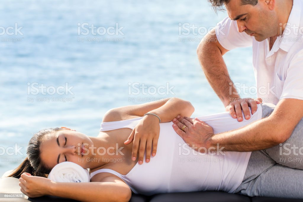 Osteopath manipulating female hip outdoor. stock photo