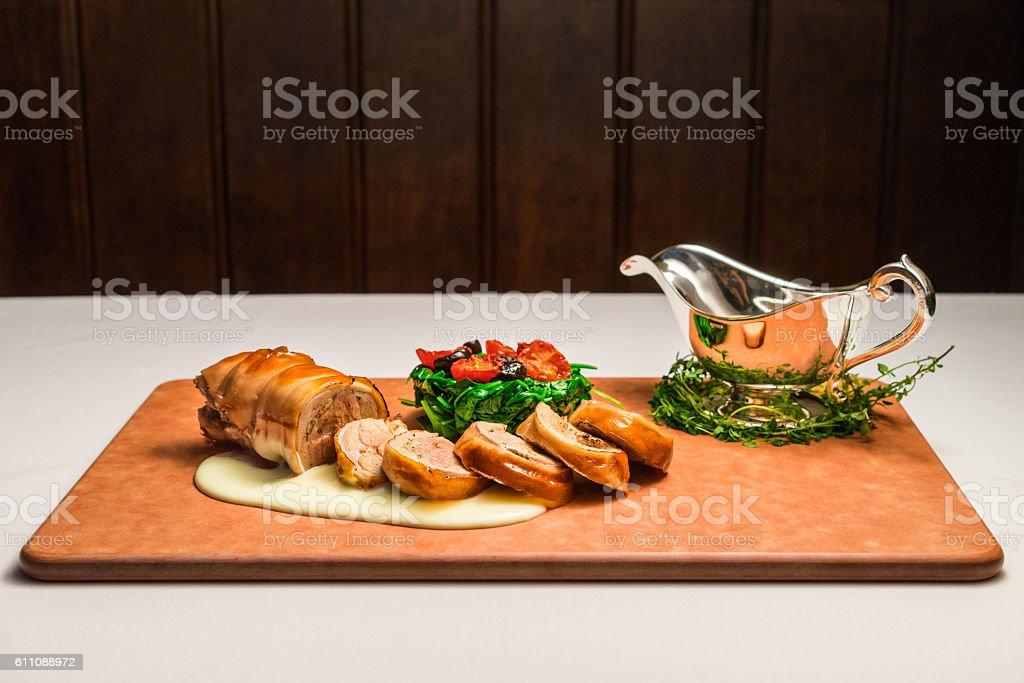 Osteria art of suckling pig porchetta on wooden cutting board stock photo