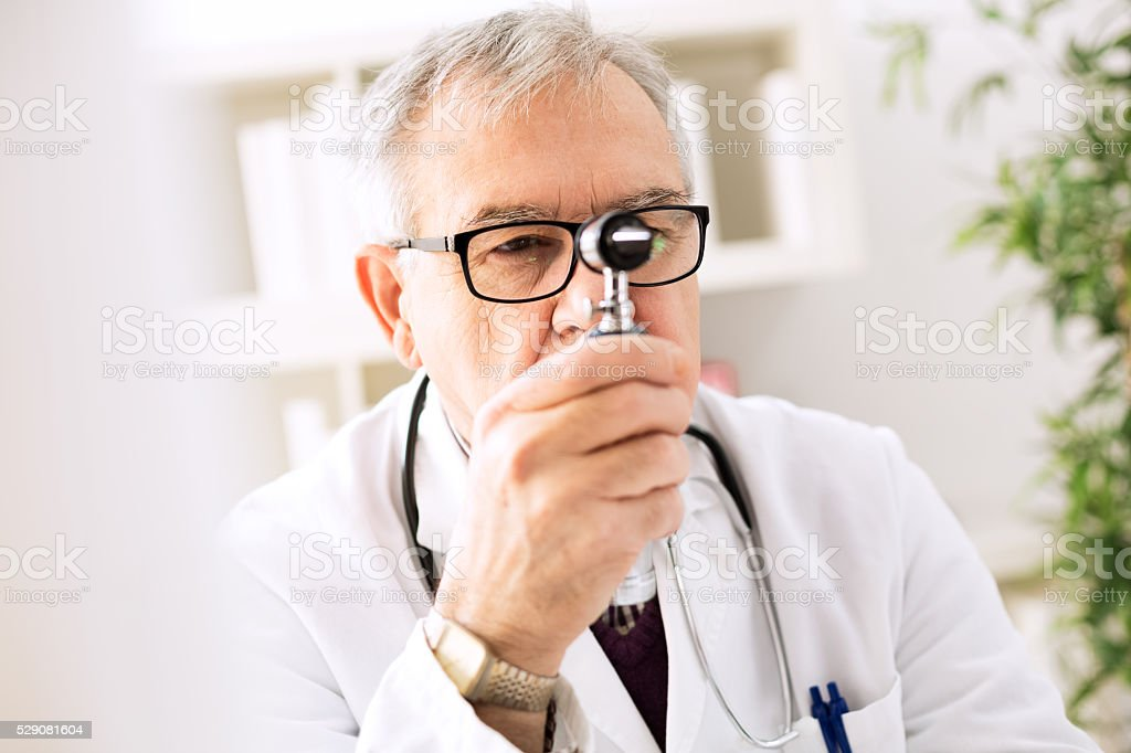 Otolaryngologist looking through otoscope stock photo