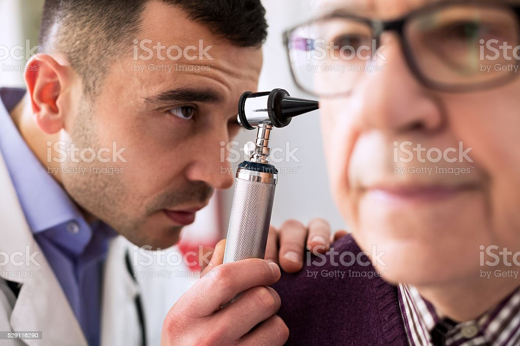 Otologist examining patient ear stock photo