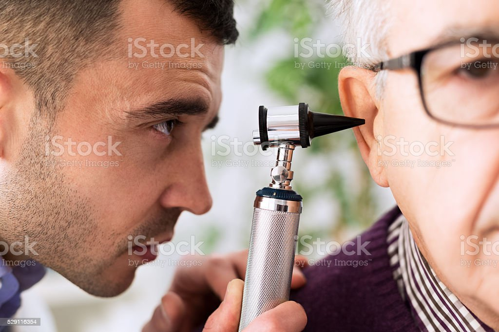 Otologist looking through otoscope stock photo