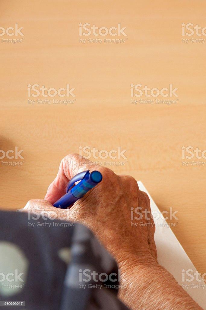 oude vrouwenhand aan het schrijven met balpen stock photo