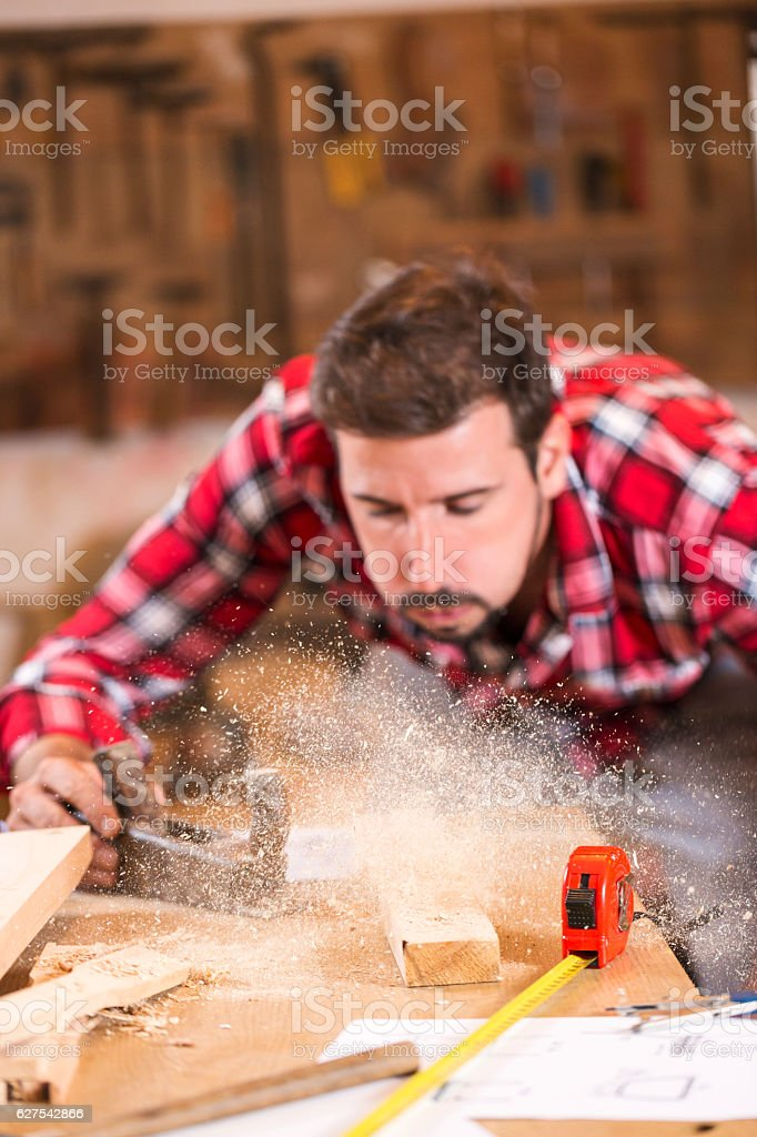 oung handosme carpenter blowing off sawdust royalty-free stock photo