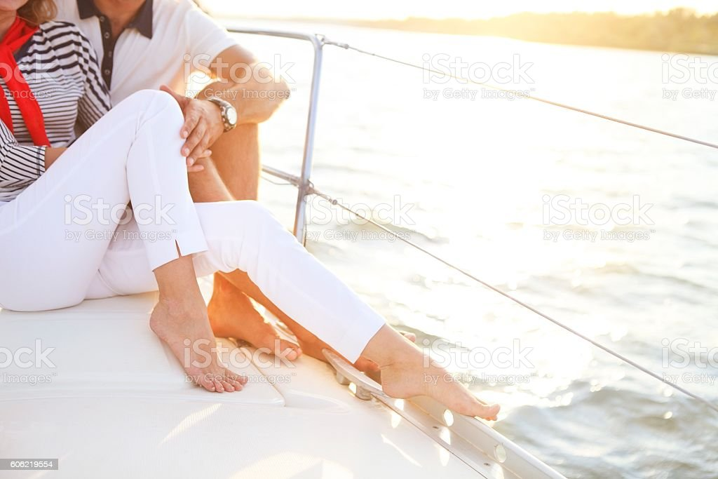 Сouple stting on sailboat deck in the sea stock photo