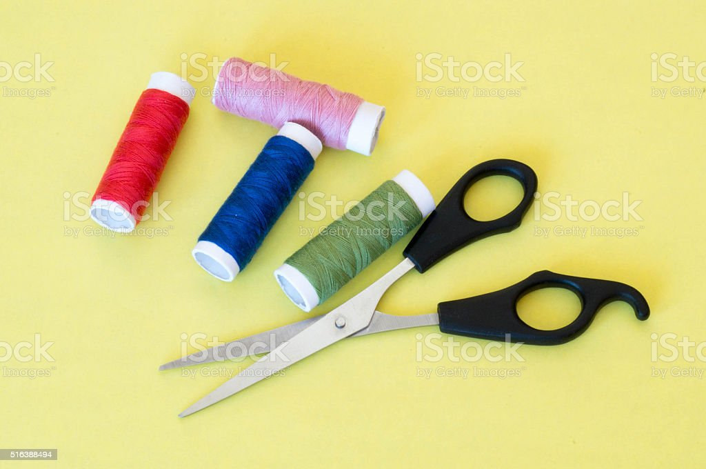 our pieces of colourful thread rolls with scissors stock photo