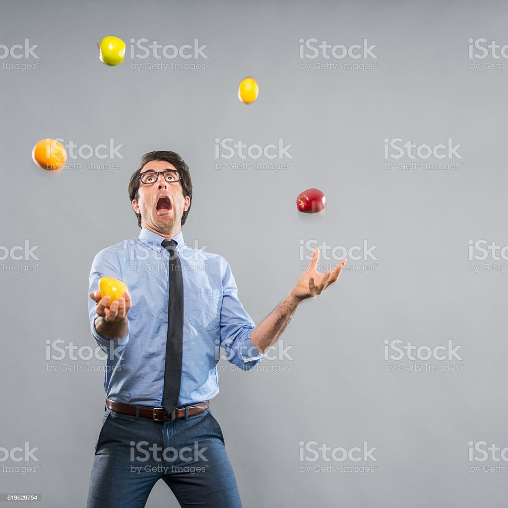 Out of Control Nerdy Businessman Juggeling Fruits stock photo