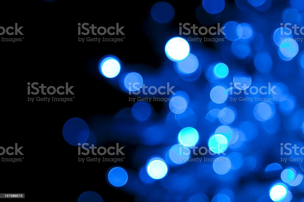 Out of focus illuminated blue dots on black background royalty-free stock photo