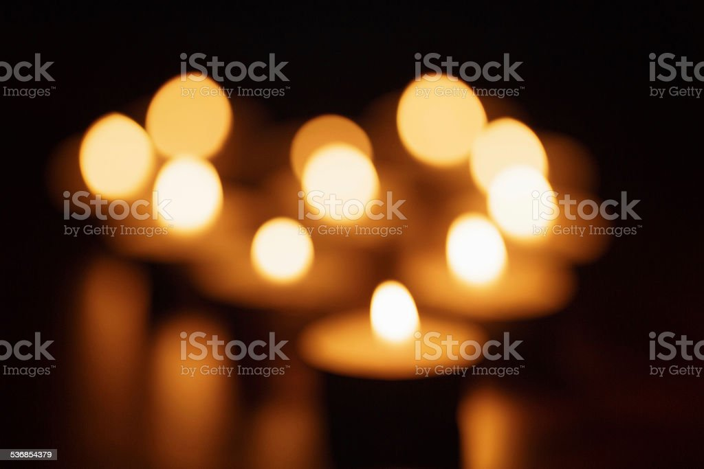 out of focus photo of burning candles stock photo