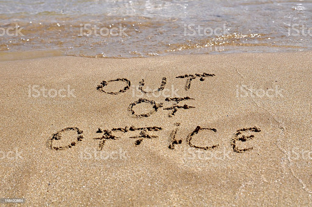 Out of office message written in the sand of a beach stock photo