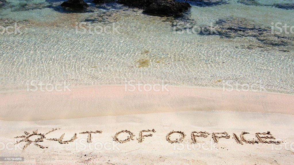 Out of office written on sand on clear beach stock photo