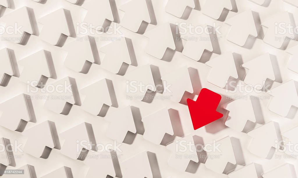 Out standing red arrow in group of white arrows stock photo
